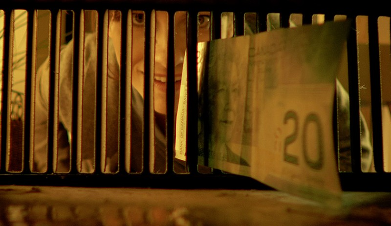 Image captured from Elusive Money green branding video. Image shows a woman reaching for a $20 bill before it slips through an air vent.
