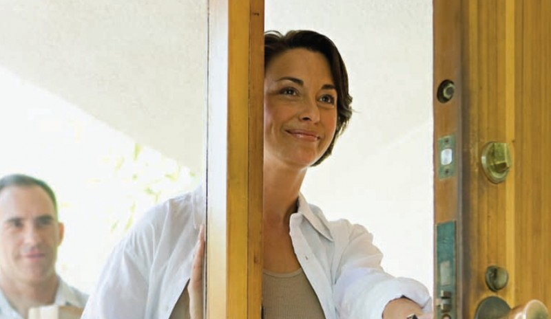 "Woman smiling, opening the door to her home. This image is from the ""Hazardcheck"" health risk awareness campaign we created for Health Canada."
