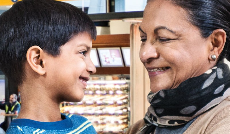 Child smiling at grandmother – image from Services to Newcomers / Super Visa campaign