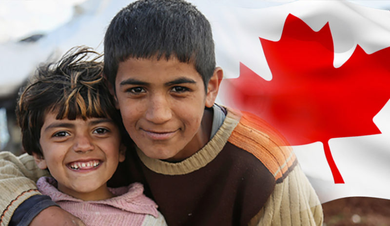 Smiling refugees in front of the Canadian flag