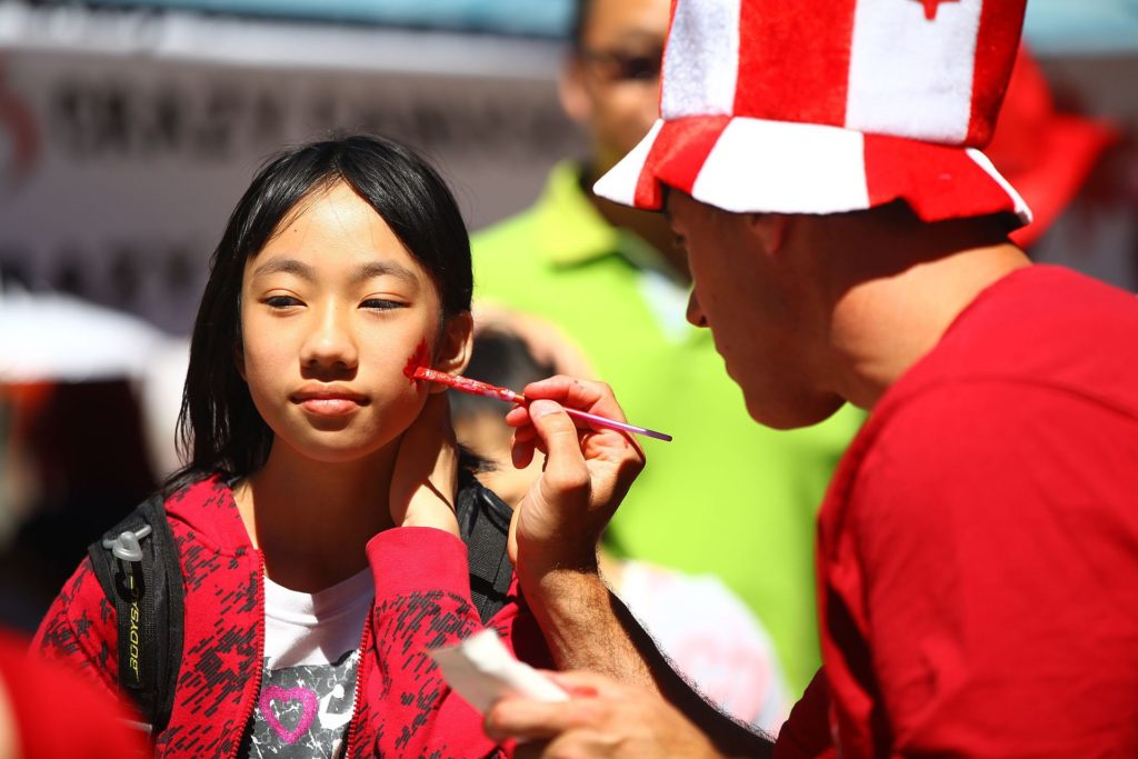 Girl getting her face painted on Canada Day