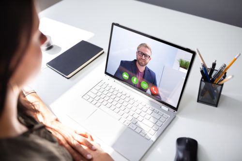 Businesswoman making video call to partner using laptop